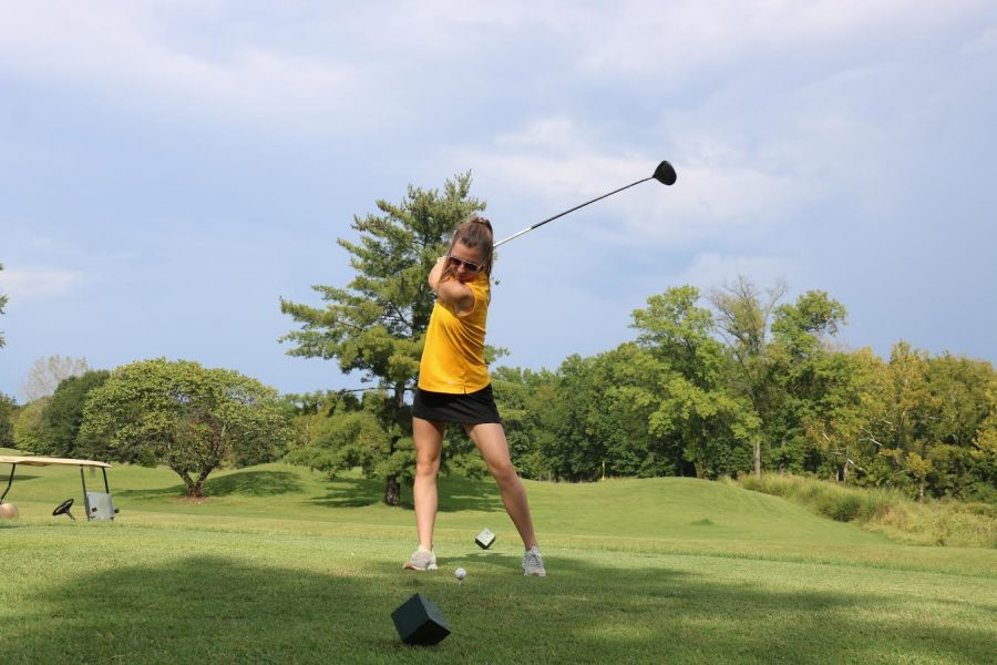 Paige Tustanowsky winding up to swing the club.