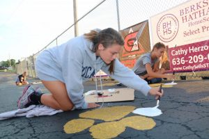 Lauren Halamicek (12) paints her paw print on the blacktop behind the football field on Sept. 4.
