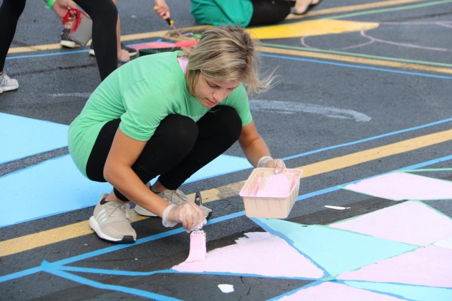 Courtney Doerr (12), who helped start the event, paints her parking spot.