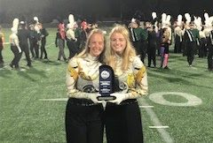 Drum majors Carley Hopkins (12) and Kayla Cormack (12)  pose for a picture with the trophy.
