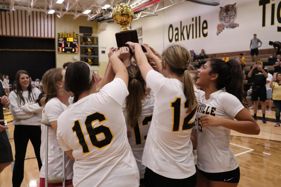 Varsity girls volleyball holds up the first place trophy after beating Marquette in the finals of the Gateway Matchup tournament.