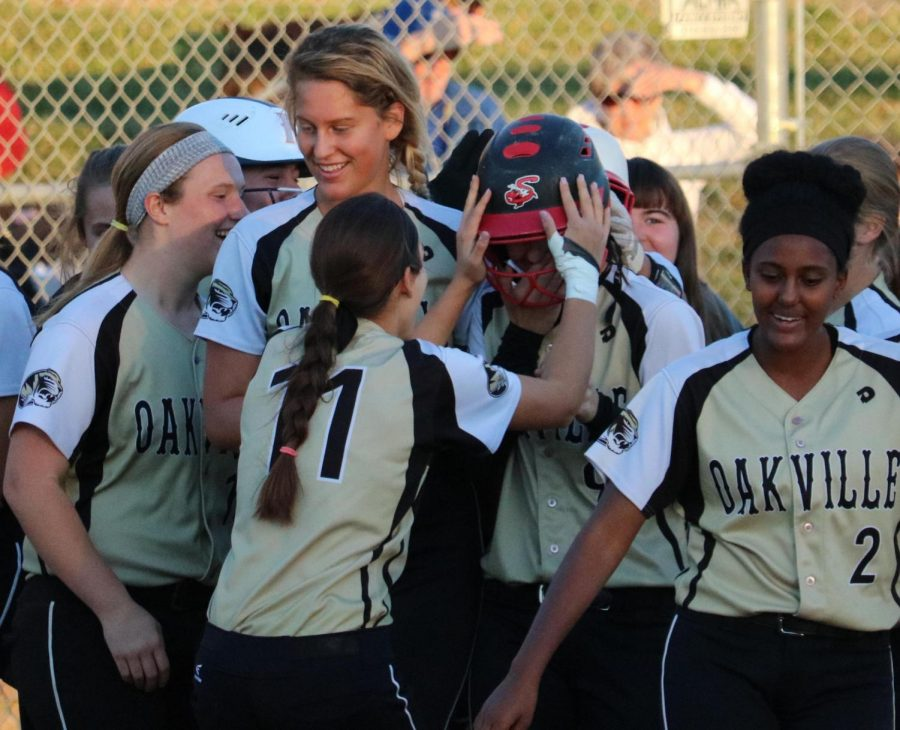 Varsity softball celebrates Amanda FitzWilliam's (12) walk-off home run.