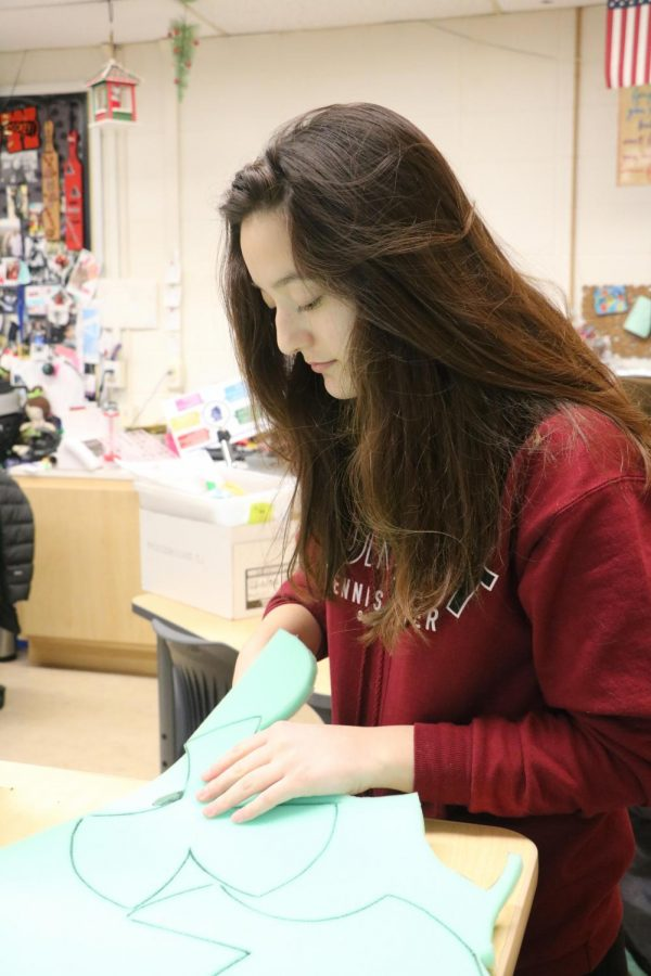Megan Blanchard (11) cuts out fabric for a project for FCCLA.