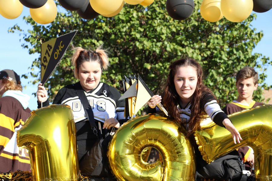 Hockey cheerleaders Chloe and Cameron West (12) hand out candy during the homecoming parade. Hockey won the All-Around Best Float award.