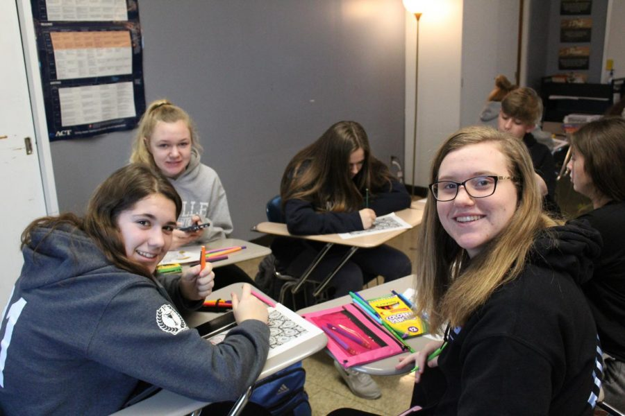 Allison Auer (9) and Sarah Hinkamp (9) color from pages in a coloring book in the Zen Coloring seminar in Mrs. Amy Crean's room. This is from the first seminar day of semester two (Jan. 27).
