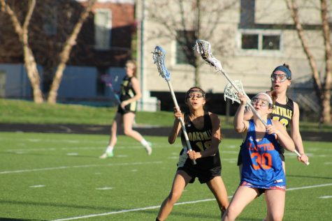Kaylene Nguyen (11) secures the lacrosse ball in her stick at a game versus Clayton.
