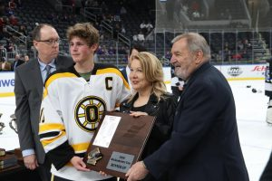 Captain Joe Pybas (12) takes a picture with St. Louis Blues legend Bobby Plager and Dianne Wickenhieser  as he accepts the runner-up plaque at Enterprise Center on March 11.