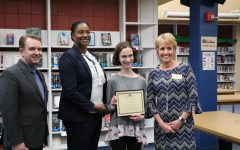 Hanna Franke (11), resieves an award for getting a perfect score on the ACT at the school board meeting on March 12.