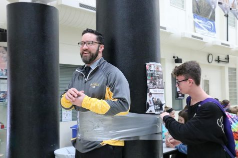 Mr. Casey Olearnick being taped to the columns in the commons during a NHS fundraiser his first year at OHS.
