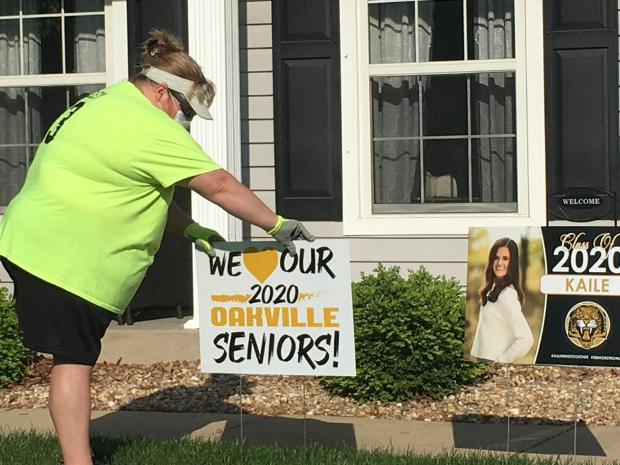 Mrs. Jackie Neeley placing a senior yard sign on the lawn of Kaile Kalton. Teachers delivered signs to all seniors on Saturday, May 2, as part of the OHS Yard Sign Brigade.