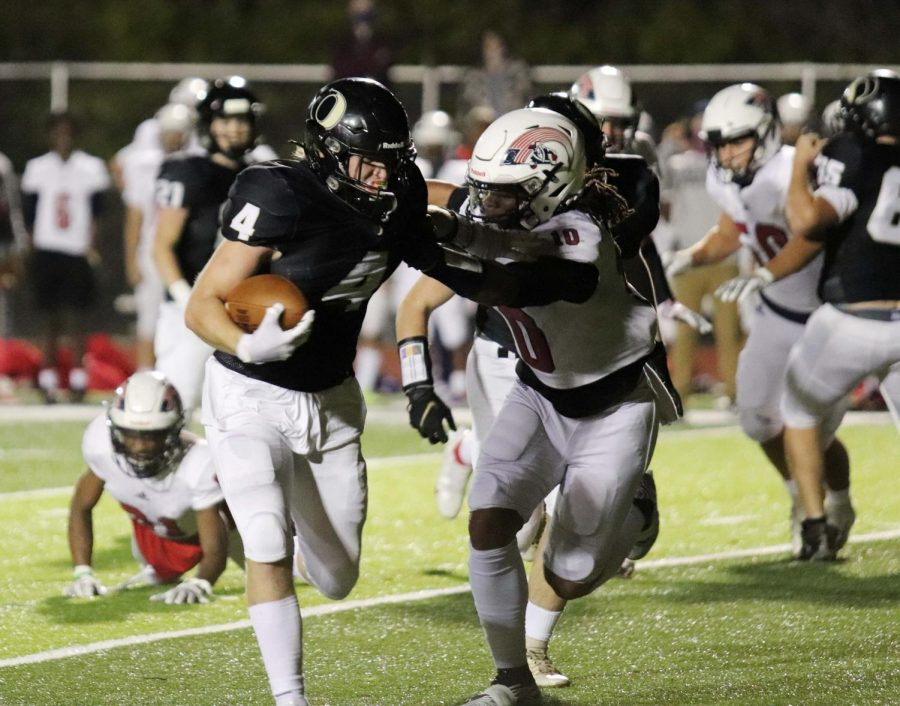 OOF. On one of many running plays, Alex Winter (12) gives a strong stiff arm to the defender while fighting for extra yards.