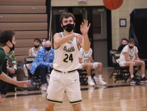 Senior Drew Elza passes the ball during a varsity basketball game, against Mehlville on Dec.18. OHS lost a close one with the final score being 60-59.