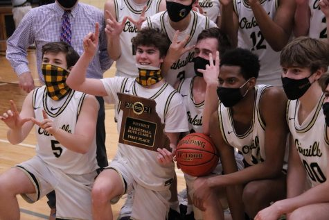 Matt Keller (12) and teammates celebrate with the district plaque after winning against the Warriors on Tuesday.
