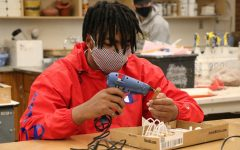 Damien Moore (12) hot glues the finishing touches on his found object sculpture for Ms. Heyl's art class.