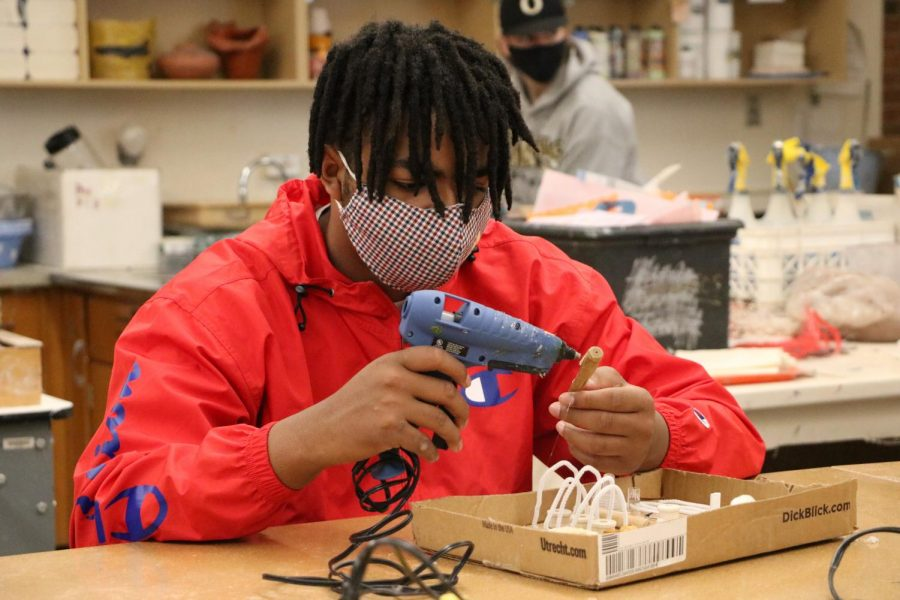 Damien Moore (12) hot glues the finishing touches on his found object sculpture for Ms. Heyl