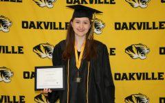 Aurora Baker (12) holding her certificate of merit for the National Merit Scholarship Program.